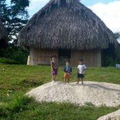 Children play in front of thatch house